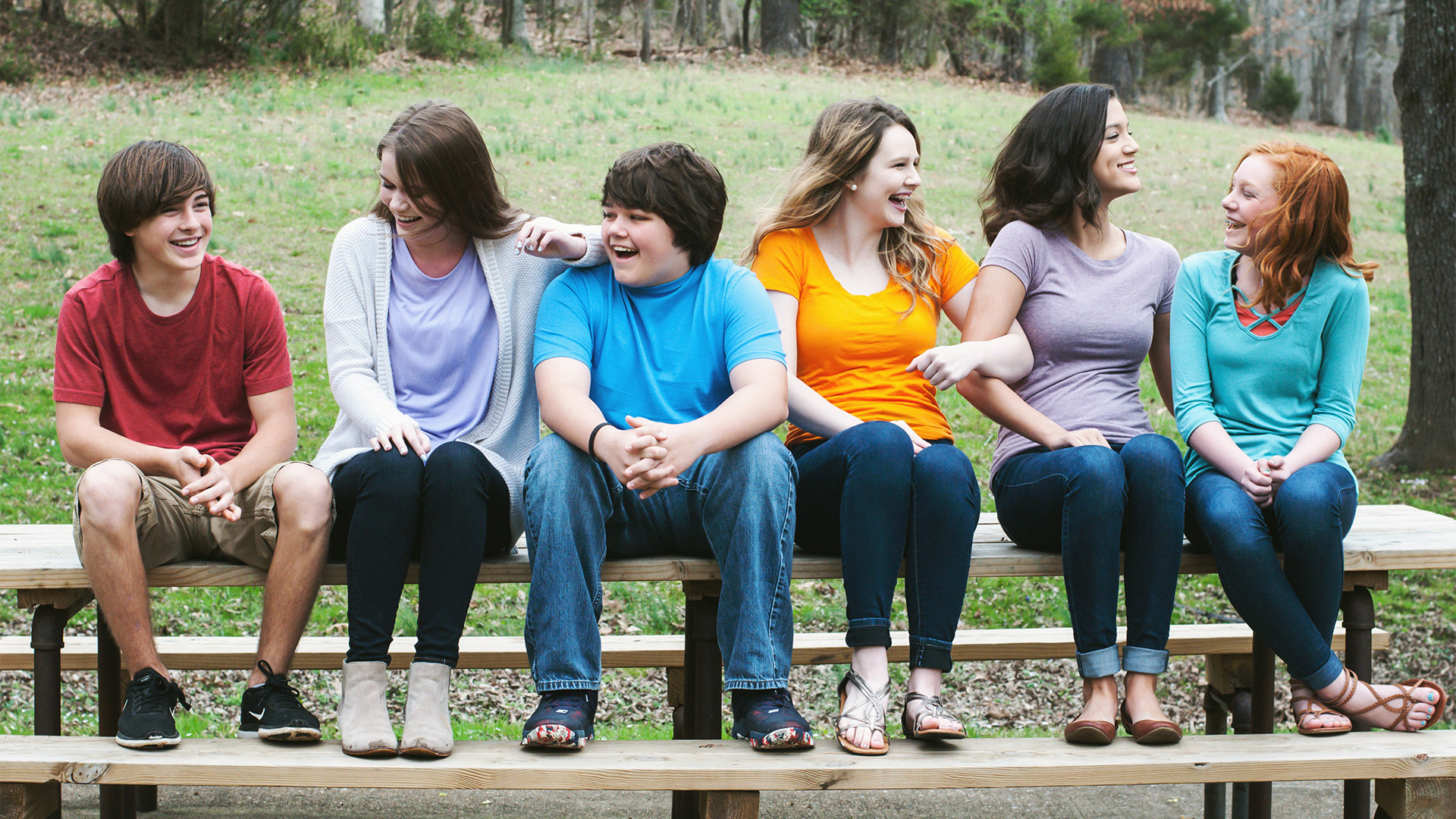 KIds smiling and laughing on a bench