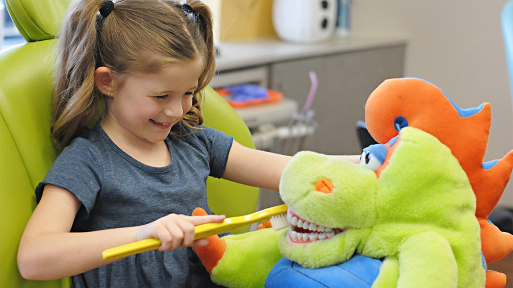 Girl brushing teeth of stuffed dragon